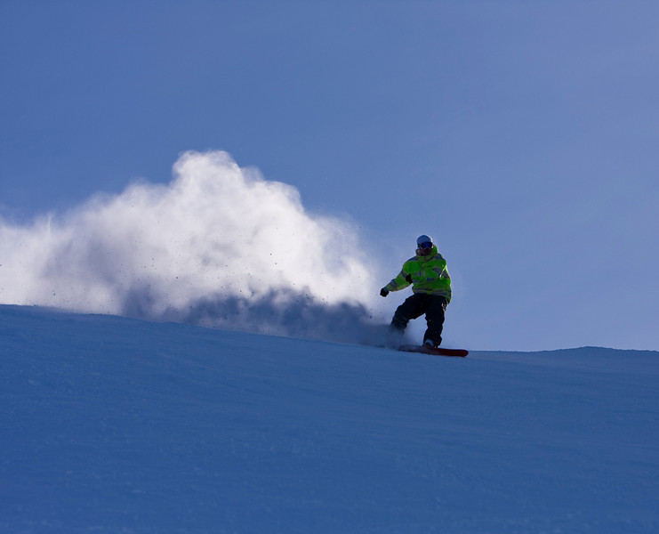 A snowboarder carving a turn at Whistler creates a huge spray of snow and ice that is backlight by the sun.