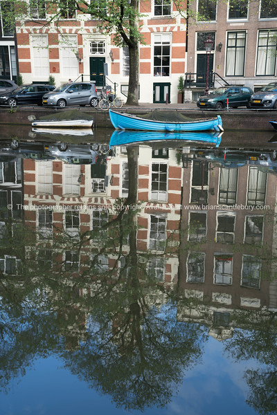 Reflection and blue boat in canals in Amsterdam