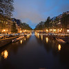 Magical effect of night lights in zoom blur reflected in calm water of Amsterdam canal lined with typical buildings
