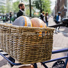 Two rounds of gouda cheese in bicycle basket