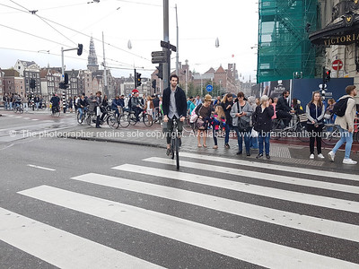 Crowd waits on city intersection on Damrak for lights to change while a cyclist starts to cross ahead.
