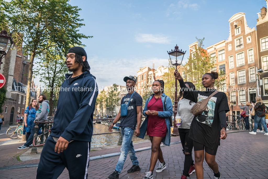 group young black tourists walking around the city taking a photo with traditional Dutch architecture behind.  Model release; no, editorial or personal use onle please