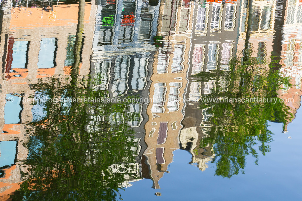 Refected architecture, Amsterdam gable facade on row houses reflections rippling in canal.