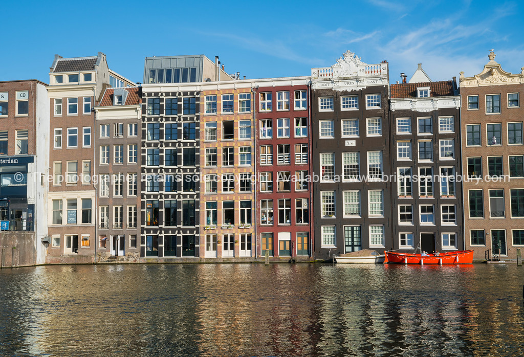 Architectural facades of a range of styles for which the city is known on other side of canal across from Damrak