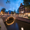 Magical effect of night lights on bridge reflected in calm water of Amsterdam canal lined with typical buildings