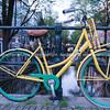 Amsterdam, Holland, yellow and green bicycle chained securely to canal bridge railing.