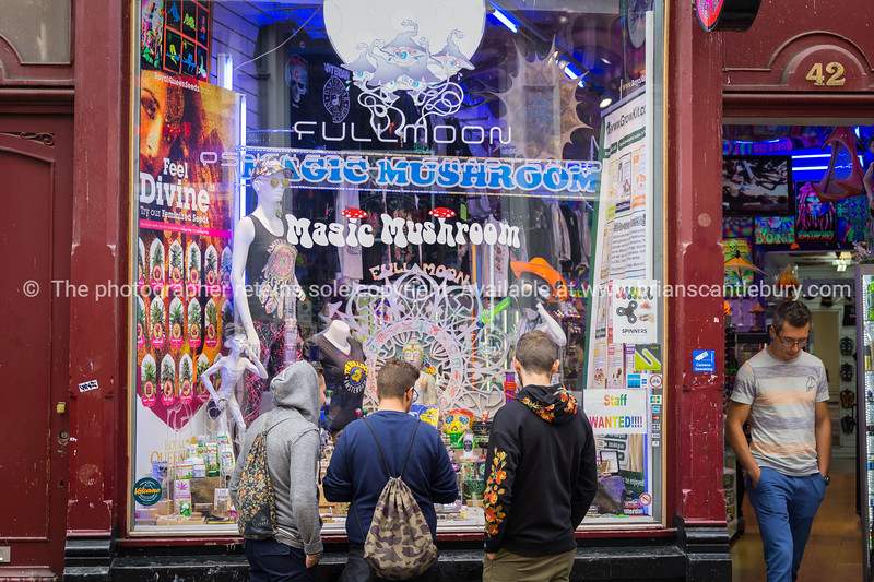 Three young guys window shop the display in shop selling range of psychedelic paraphenalia;  Model or property release; NO, for personal or editorial use only please.