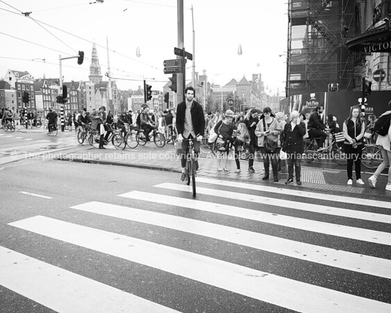 Mobile perspective cyclist in striped tee- shirt rides across crosswalk while pedestrians wait