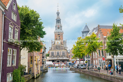 Historic ornately decorated Waag, or weigh house, surrounded by crowd people at end of canal lined by commercial and residential buildings.