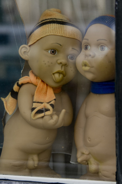 Weird naughty dolls in a window. Uncircumsized.