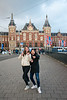 Two girls stike a pose in front of the Amsterdam, Centraal Station. Amsterdam, Netherlands, Europe.