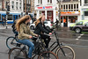 Girls and others riding cycles in the streets of Amsterdam, Netherlands, Europe.
