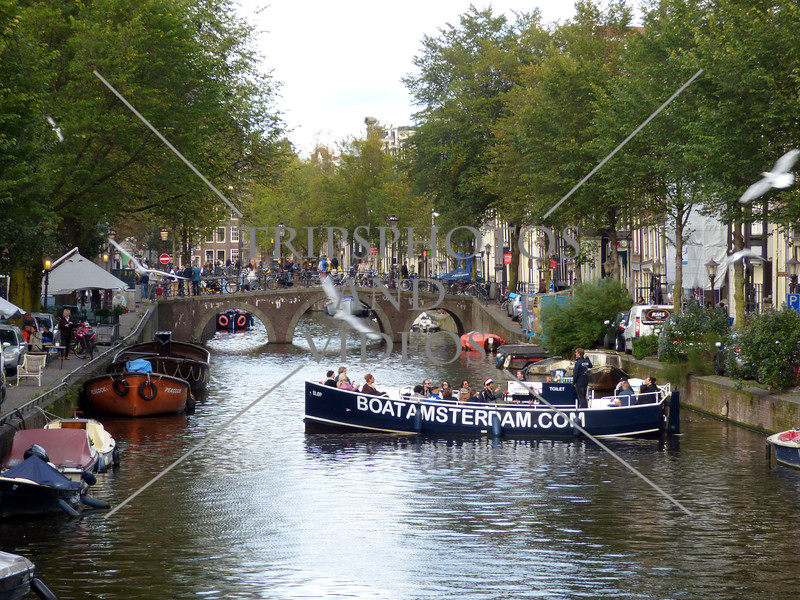 A canal tour boat and bridge in Amsterdam, Netherlands.