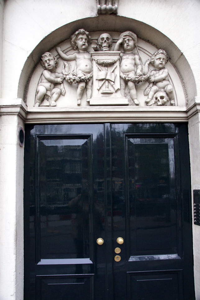 Carvings(?) over door of building, probably apartments.