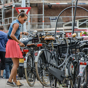Not a great image but I just loved the juxtaposition of this young woman in her darling coral skirt, tennies and cut out jean jacket with the rest of the bikes.