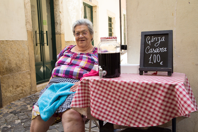 A lady sells homemade Ginja in the streets of Alfama, Lisbon