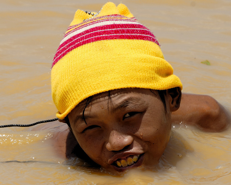 A young boy harvests bottom feeders, Tonle Sap lake, Cambodia.