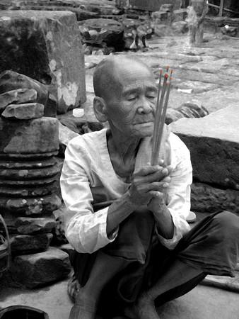 Angkor wat female nun praying with incense, Cambodia