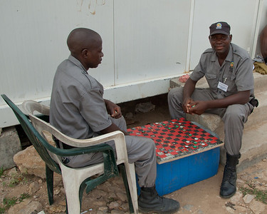 "These guys are ""guarding"" the old Portuguese fort in Luanda.  Those are beer bottle caps that they're playing with; one player uses the caps right side up while the other player uses them upside down."