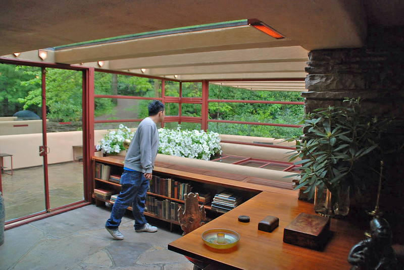 Desk and bookcase built into the living room area.  The white flowers are over the staircase that leads down to the stream.  The glass panels to the right of the flowers roll back under the flowers to open the staircase.