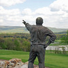 A statue of Joseph Hardy, III, founder of 84 Lumber, points to the countryside of his Nemacolin Resort.