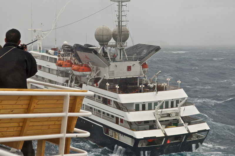Clelia II in the Drake Passage.  NG Explorer in process of sending a satellite phone over to her. (Note white cord upper left being carried over by a rocket. Sat phone is attached to cord.)
