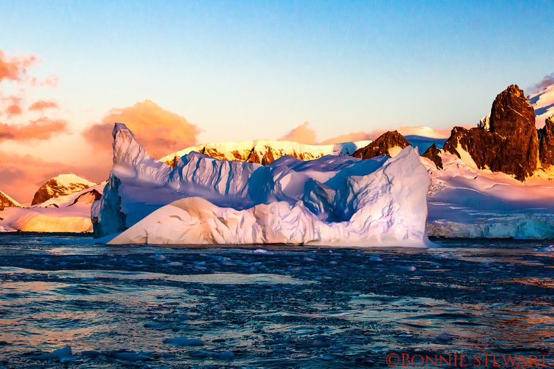 Sunset in Antarctica with blue waters and an iceberg