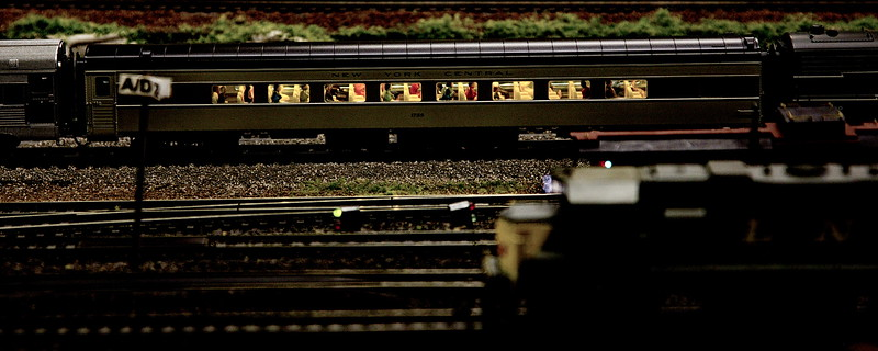 A passenger train passes under yard lights at night.
