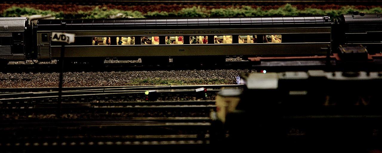 A passenger train passes under yard lights at night.