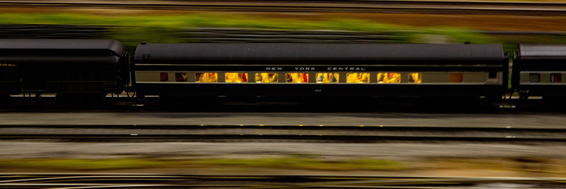 A New York Central passenger train zooms by at dusk, with its passengers visible inside a lighted car.