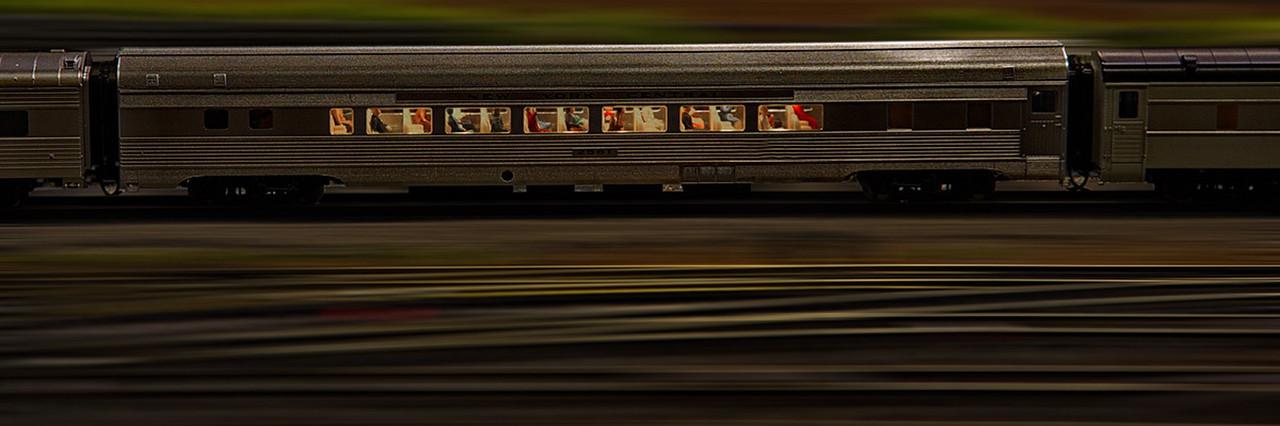 A passenger train passes by at dusk.