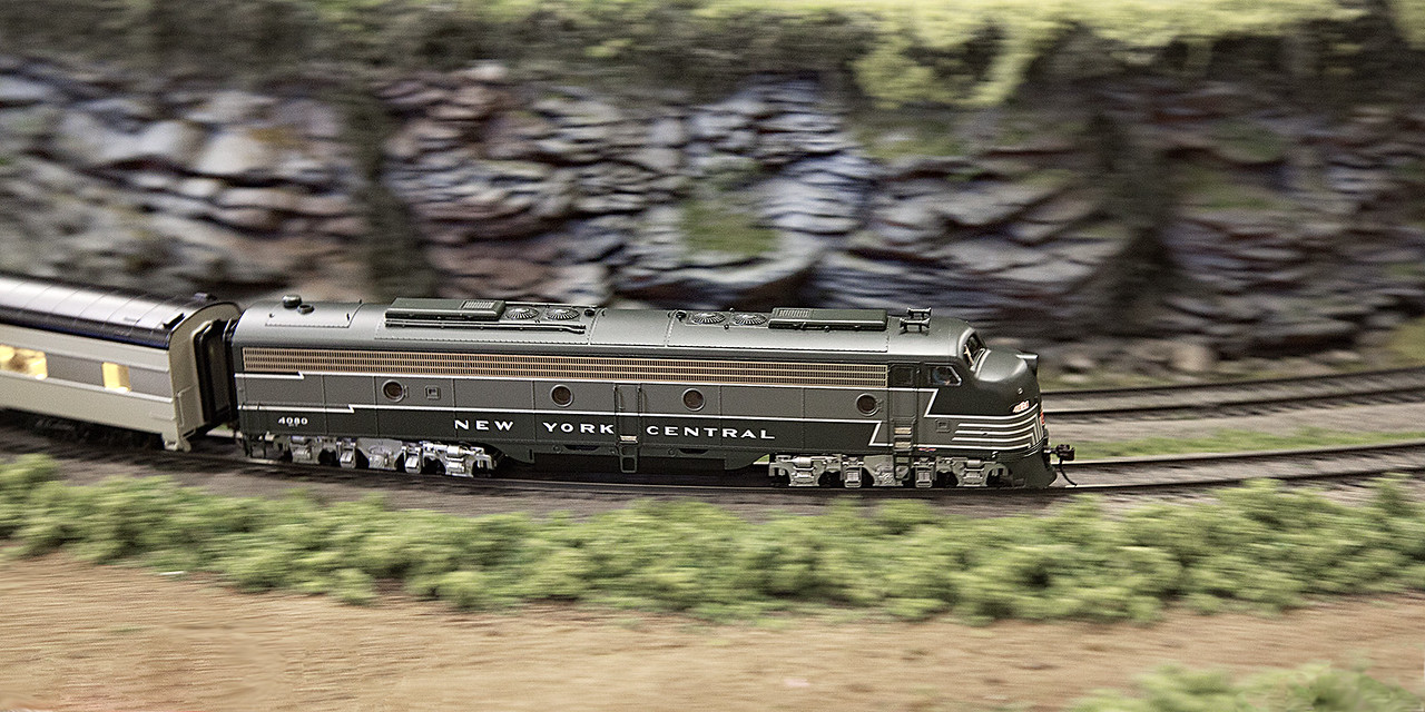 A New York Central diesel engine pulling a passenger train rounds a bend.