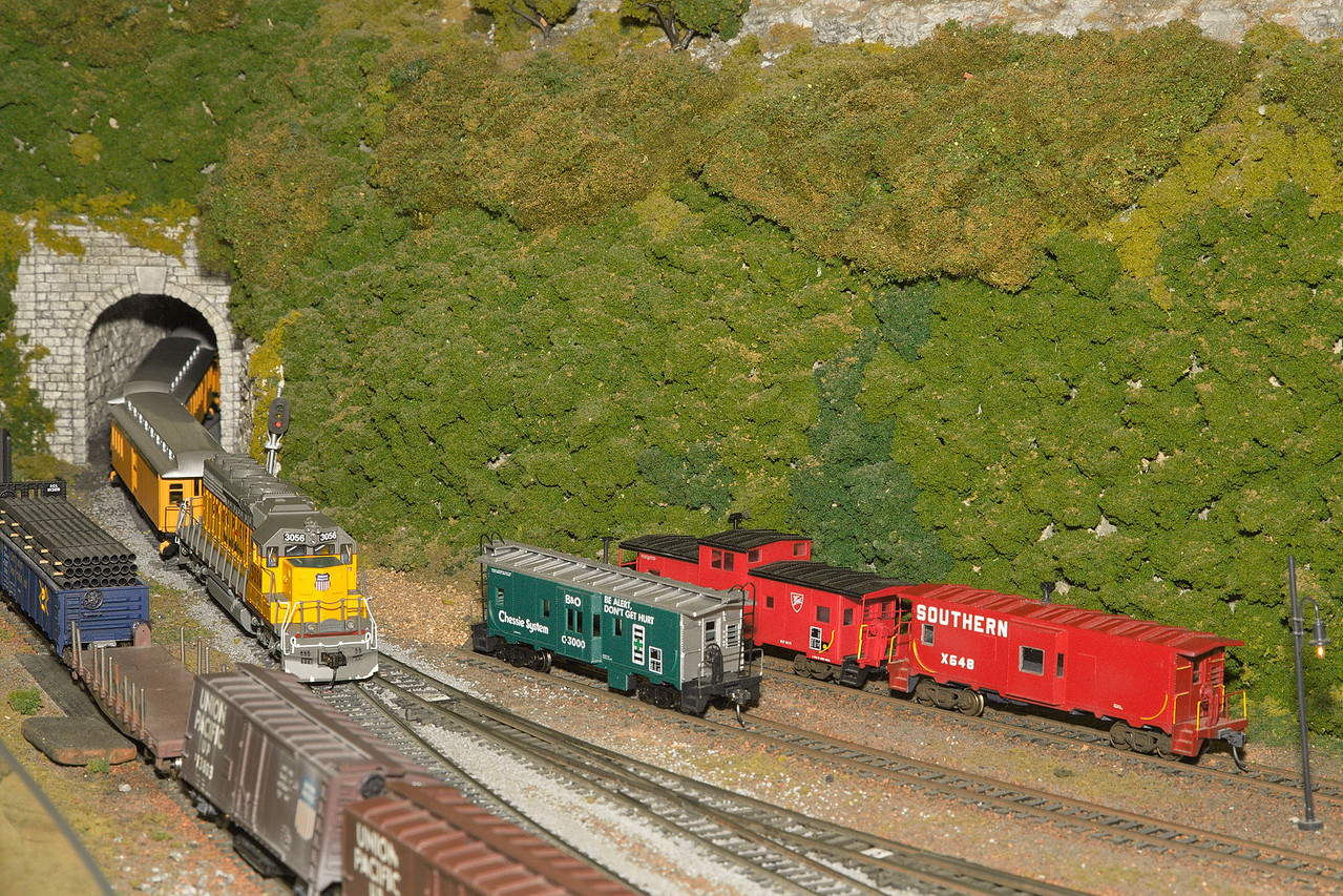 A Union Pacific passenger train, pulled by a diesel engine, exits a tunnel.