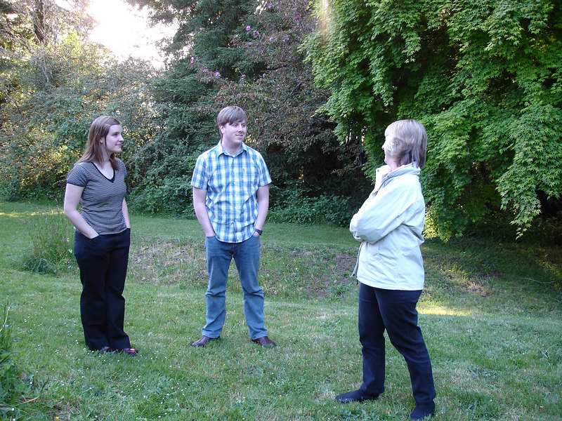 Pam talking to Caitlin and Winslow in their backyard.