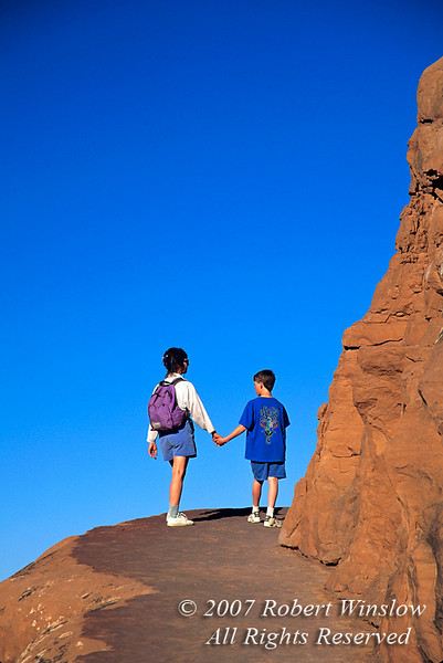 Woman and Boy age 10 Hiking, Delicate Arch Trail, Arches National Park, Moab, Utah, USA, North America