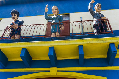Diego Maradona, Evita Duarte Peron, and the poet Carlos Gardel on a balcony in La Boca, Buenos Aires