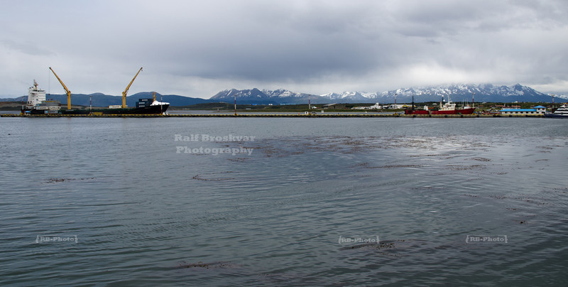 A container vessel is being loaded at the tourist pier in Ushuaia harbor, Tierra del Fuego, Patagonia, Argentina
