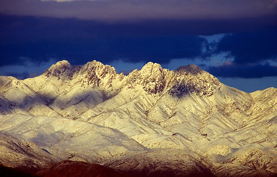 The jagged skyline of Four Peaks in the Mazatzal Mountains with a dusting of snow  photographed from Fountain Hills, Arizona, Southwest United States