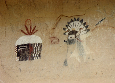 Zuni Rock Art, Zuni Petroglyphs and Zuni Pictographs  On the left is Hehe'a, the Blunderer kachina, a clown.  On the right is a Shalako, an important ceremonial figure. Shalakos are couriers from the rain gods. The Shalako Dance Rite is held in December.   These pictographs are on a sandstone overhang near an ancient site known as Village of the Great Kivas on the Zuni Pueblo.