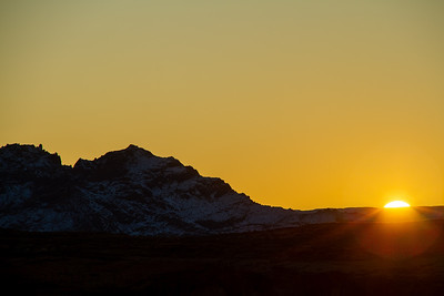Sun setting on the horizon with a snow covered mountain