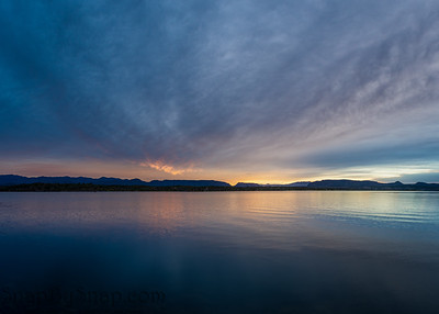 The sun rising over a lake with the colors of sunrise reflecting off the clouds and the water