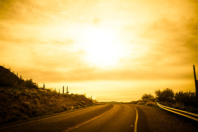 A brilliant sunrise over a road on a hilltop with saguaro cacti on the sides of the road