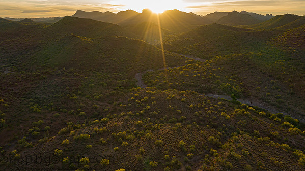 Aerial over the Arizona desert during sunset with mountains