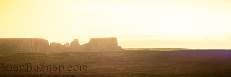 Panoramic image of the morning sky over a barren desert with mesas in the distance