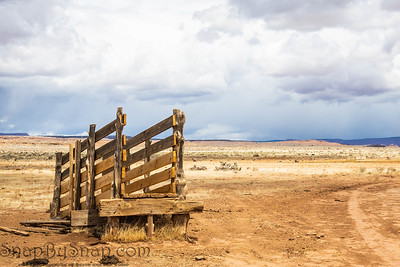 An old corral, abandoned in the desert of Arizona under a blue sky with bright white