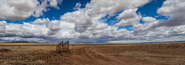 A panorama of an old corral, abandoned in the desert of Arizona under a blue sky with bright white