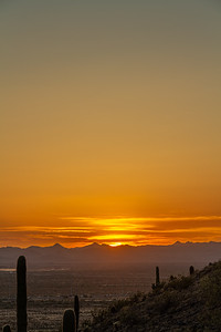 The sunsetting over distant mountains with an orange glow in the sky