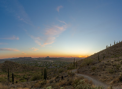 A desert trail on a mountain leading to a sunset over a valley in Phoenix