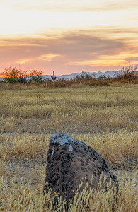 A rock sitting in the desert of Arizona with an evening sky