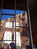 Windows give a view through the chapel's front windows while reflecting the red rocks in back.